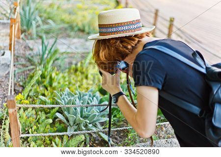 Young Inquisitive Woman Turists Photographs Exotic Plant In A Garden Outdoor