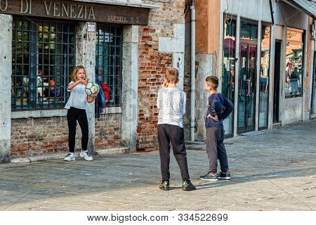 Children Playing Football On The Streets Of Venice.