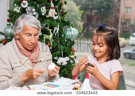 Little Girl Having Fun While Making Christmas Nativity Crafts With Her Grandmother - Real Family