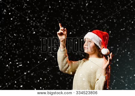 Teenager Girl Young Woman In Red Cap And Knitted Sweater Is Touching Snowflakes With Her Finger Enjo