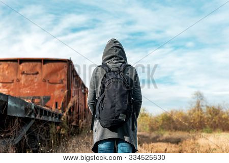 Homeless Woman With Backpack Getting Away From It All, Rear View Of Female Walking Among Abandoned T