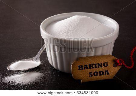 Baking Soda In White Bowl On Black Background