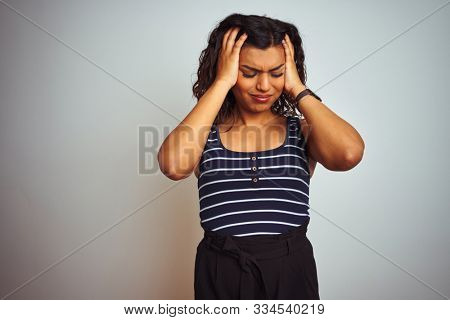 Transsexual transgender woman wearing striped t-shirt over isolated white background suffering from headache desperate and stressed because pain and migraine. Hands on head.