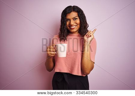 Transsexual transgender woman drinking cup of coffee over isolated pink background very happy pointing with hand and finger to the side