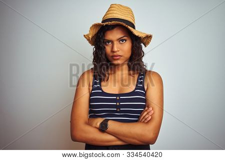 Beautiful transsexual transgender woman wearing summer hat over isolated white background skeptic and nervous, disapproving expression on face with crossed arms. Negative person.