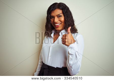Beautiful transsexual transgender elegant businesswoman over isolated white background doing happy thumbs up gesture with hand. Approving expression looking at the camera with showing success.