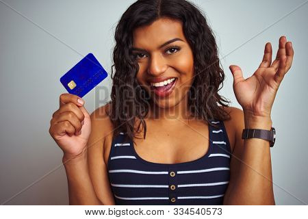 Transsexual transgender customer woman holding credit card over isolated white background very happy and excited, winner expression celebrating victory screaming with big smile and raised hands