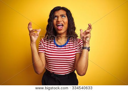 Transsexual transgender woman wearing stiped t-shirt over isolated yellow background crazy and mad shouting and yelling with aggressive expression and arms raised. Frustration concept.