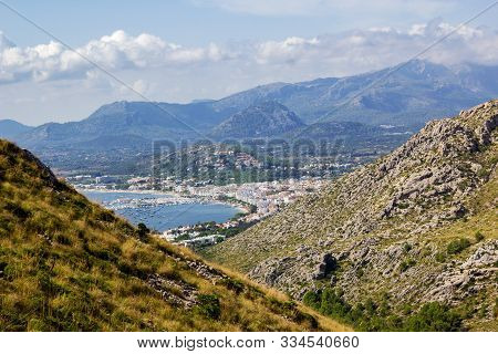 View Of Port De Pollenca Through Hills With Mountains In Background At Mirador Es Colomer, Mallorca,