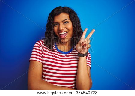 Transsexual transgender woman wearing stiped t-shirt over isolated blue background smiling with happy face winking at the camera doing victory sign. Number two.