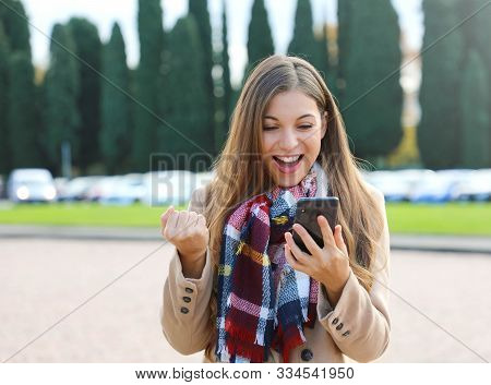 Happy Success Woman Celebrating Outdoor Cheering And Raising Her Fist Up In Exultation. Excited Fash