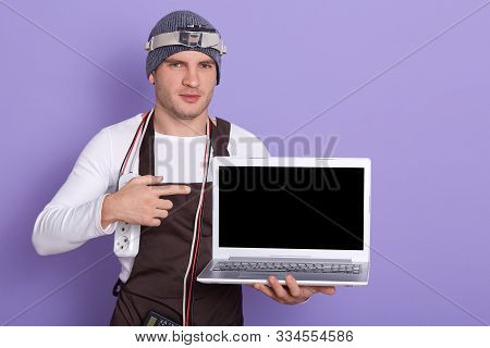 Young Radioman Wears White Casual Shirt, Cap And Apron, Poins At Blank Screen Of Laptop Over Lilac B