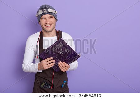 Young Smiling Electrician After Checking Serviceability Of Motherboard, Using Multimeter And Magnifi
