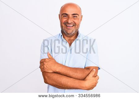 Middle age handsome man wearing casual shirt standing over isolated white background happy face smiling with crossed arms looking at the camera. Positive person.