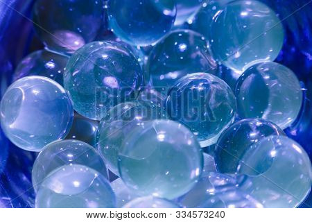 Water blue gel balls. Polymer gel. Silica gel. Balls of blue hydrogel. Crystal liquid ball with reflection. Texture background. Close up macro poster