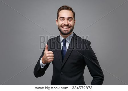 Smiling Young Bearded Business Man In Classic Black Suit Shirt Tie Posing Isolated On Grey Backgroun