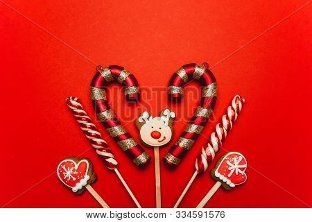 Christmas Sweets On A Red Background: Gingerbreads In The Shape Of Mittens And Deer, Lollypops. Fest