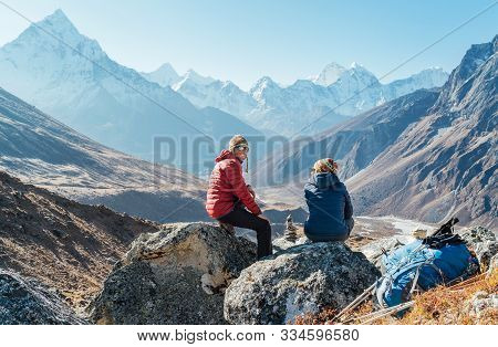 Cute Couple Resting On The Everest Base Camp Trekking Route Near Dughla 4620m. Man Smiling To Woman.