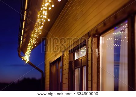 Cozy Scene Of String Lights Hanging Under The Roof At Evening Time. Fashion Decoration With Bulbs Fo