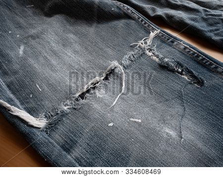 A jeans with Frayed or torn knee.