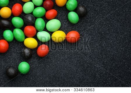 Colorful Background Assorted Rainbow Peanuts In Chocolate, Top View On A Black Shiny Background. Top