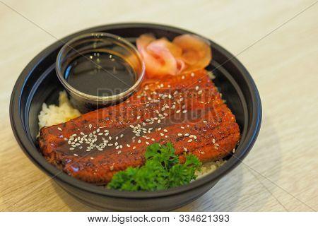 Unadon Or Unagi Donburi With Pickled Ginger In Black Plastic Bowl For Take Home.