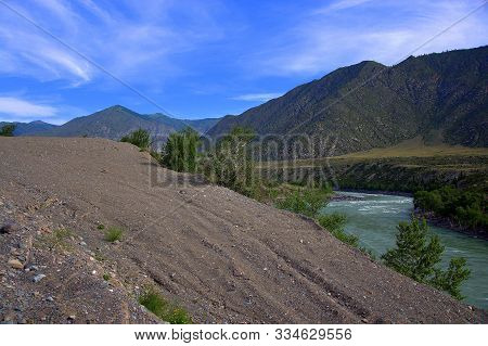 View From The Top Of The Hill To The Turquoise River Flowing Through The Mountain Valley.