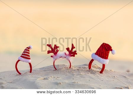 Christmas Santa Hats And Reindeer Antler Headbands Standing In The Sand On A Beach In Summer. Beach