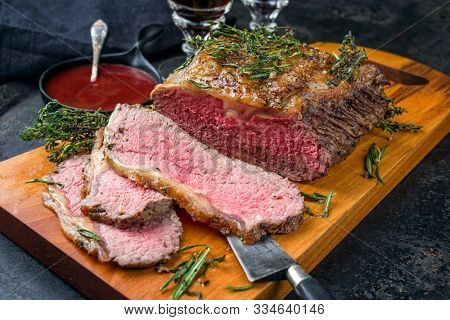Traditional Commonwealth Sunday roast with sliced cold cuts roast beef with herbs and red wine as closeup on a modern design wooden board