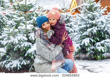 Cute Little Smiling Kid Girl And Mother On Christmas Tree Market. Happy Child, Daughter And Young Wo