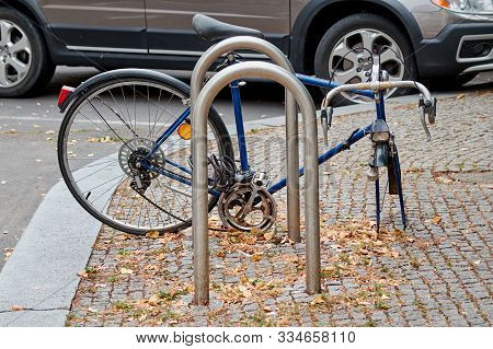 Bike With Stolen Wheel Parked Near To The Bicycle Parking. Broken Bike, Stolen Bicycle.