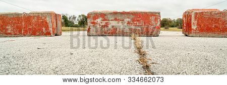Heavy concrete roadblocks blocking highway or street. Obstacle, dead end  or obstruction to progress concept. Panoramic banner.