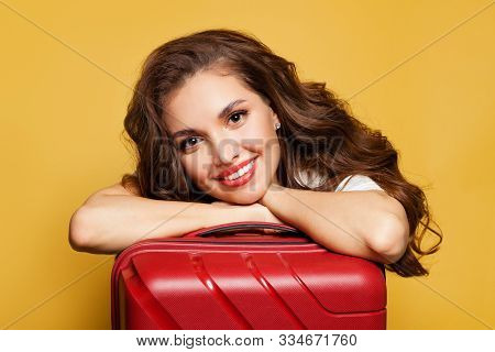 Cheerful Girl Traveler Tourist With Red Suitcase On Bright Yellow Background. Pretty Woman Passenger