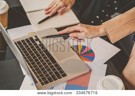 Top view of closeup asian businesswomen holding and pen pointing to technology laptop in modern meeting room, office or working space when working with the partner business, coffee break, partner and colleague concept poster