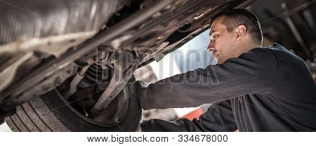 Auto Master Mechanic Checks Condition Of The Brakes And Wheels