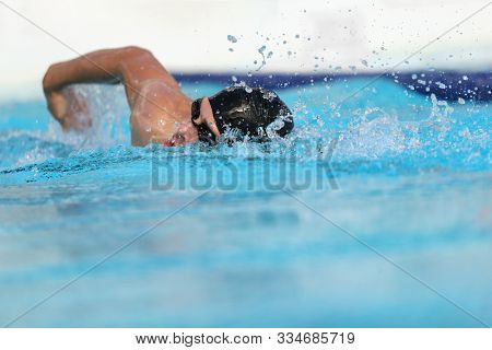 Swimming pool athlete training indoors for professional competition. Swimmer man on swim practice in stadium doing crawl with arm splashing water. Copy space on blue water background.