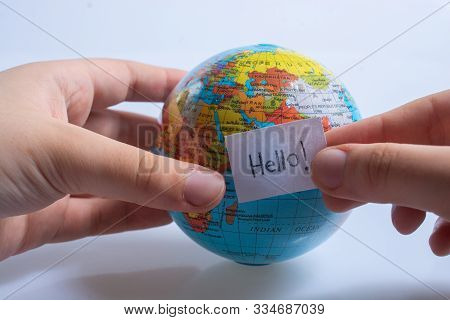 Hand Holding Notepaper With Hello Wording On Model Globe