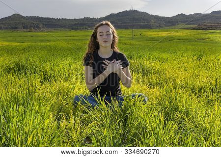 Young Caucasian Woman Red-haired With Freckles, Resting On A Green Field At Spring Sunset, Sitting I