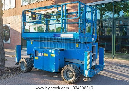 Blue Scissor Lift Aerial Work Platform At Street