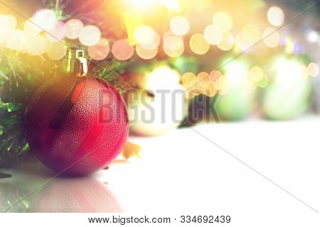 Close Up Of Red Ball Decorated At The Christmas Tree On Bokeh Light Background With Copy Space