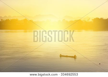 Silhouette Fisherman Boat In Sunrise At Mekong River In Thailand, Peacefulness In Nature.