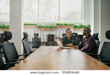 Two Businessmen Sitting At Boardroom Table For Meeting Discussing Information On Laptop With Copyspa