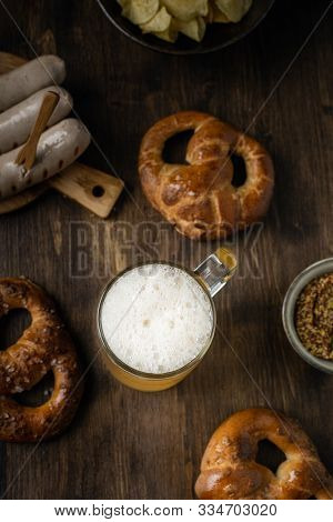 Beer Glass With Pretzels, Bratwurst And Snacks On Rustic Wooden Table, Top View, Oktoberfest