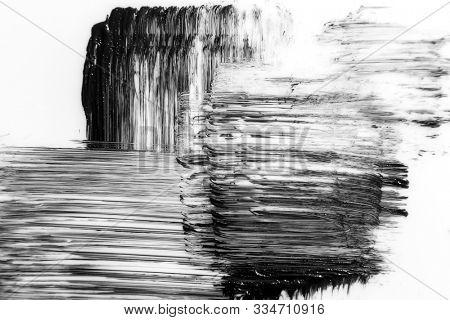 Black strokes and texture mascara or acrylic on a white background. Texture of black mascara for eyelashes isolated on white background. Smear of black mascara for eyelashes on white. Mascara smears