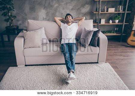 Photo Of Mixed Race Arabian Guy Sitting Cozy Sofa Holding Hands Behind Head Relaxing Homey Weekend M
