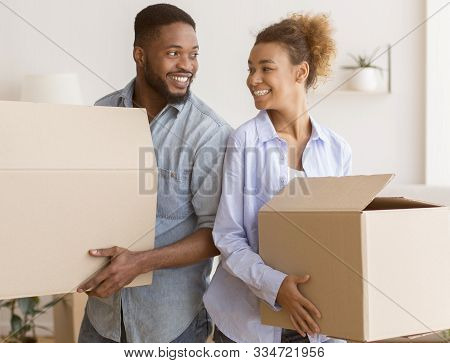 Moving House. Happy Black Couple Holding Packed Boxes Smiling Each Other Standing Back-to-back In Ne