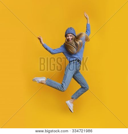 Breezy Girl In Blue Winter Clothes Jumping In The Air, Showing Funny Moves, Yellow Studio Background