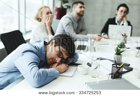 Boring Presentation. Business Man Sleeping And Female Colleague Yawning During Meeting In Office