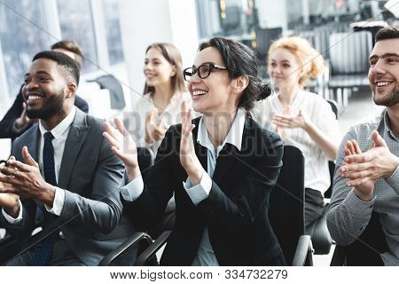 Business Lecture. Happy Executives Applauding To Speaker, Listening His Speech In Boardroom