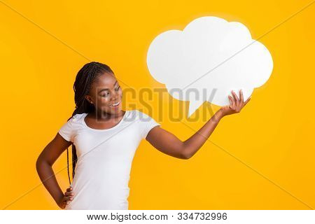 Pretty Interested Girl Holding Communication Bubble And Looking At It, Yellow Studio Background